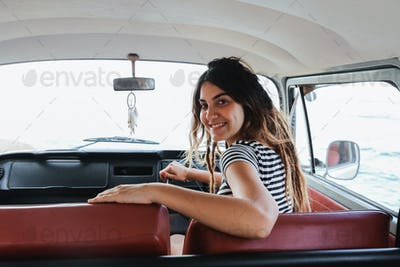 young woman driver smiling and look back on road trip