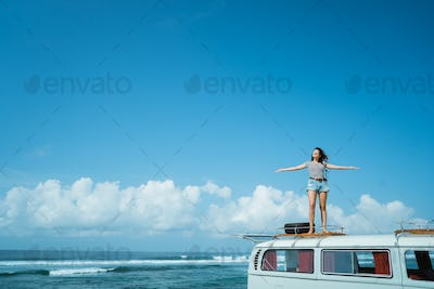 Beautiful woman raise hands enjoy road trip nature standing on t