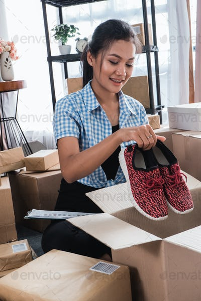 woman packing of shoes on carton boxes