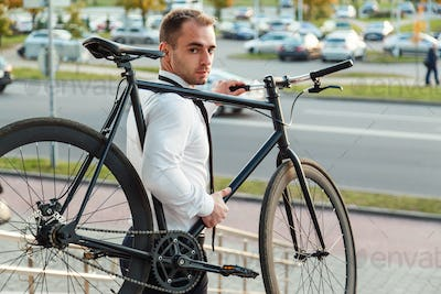 Handsome young businessman in a white shirt and black tie carries his bike