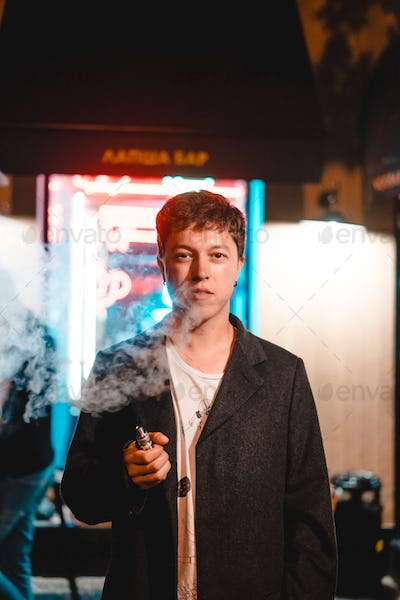 Man smokes electronic cigarette and looks at the camera