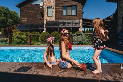 Happy mother and two daughters in swimsuits at border of pool