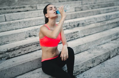 Thirsty sportswoman doing her jogging training