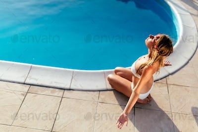 Blond woman meditating at pool