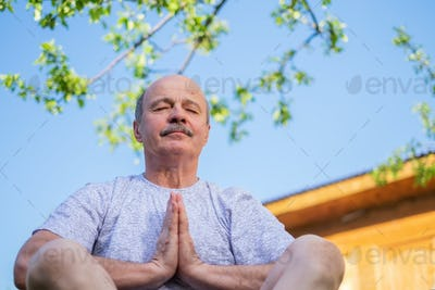 Peaceful senior man meditating seated ooutdoor under the tree. Concept of mental health