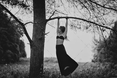 Monochrome photo of young woman hanging on branch of tree.