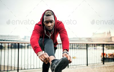 A young sporty black man runner tying shoelaces outside in a city.