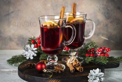 Mulled wine in glass mug with fruit and spices