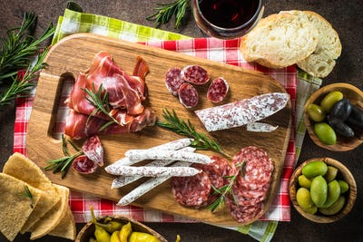 Antipasto - sliced meat, ham, salami, olives on dark stone table