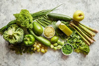 Green antioxidant organic vegetables, fruits and herbs placed on gray stone