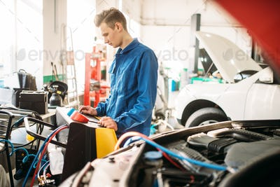 Mechanic checks air conditioning system in car