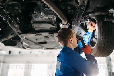 Mechanic with lamp checks car brake hoses