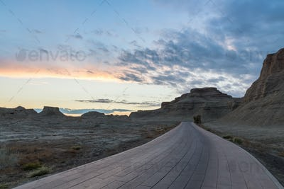 xinjiang ghost town in sunset, wind erosion landforms landscape and road