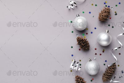 Christmas balls and pine cones on grey background