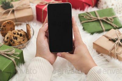 Christmas application. Woman using smartphone mockup, copy space