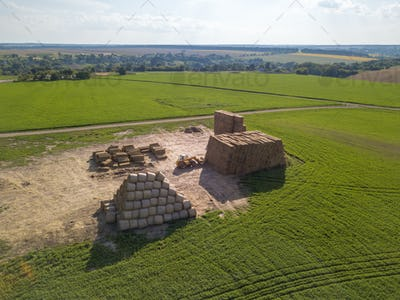 Green field with large haystacks and tractor on a sunny day. Aerial view from the drone