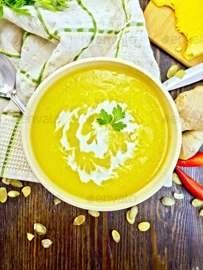 Soup-puree pumpkin with cream and parsley in bowl on board top