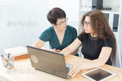 Women sitting and discussing ideas at the office with laptop, looking at the screen