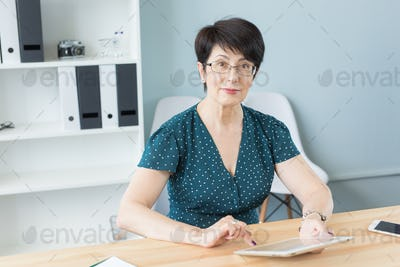 Business and people concept - middle aged confident woman is working with tablet in office