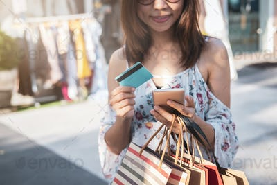 Young woman using smartphone with shopping bags and credit card at shopping mall