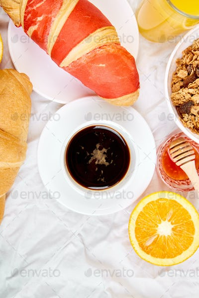 Good morning. Continental breakfast on white bed sheets.