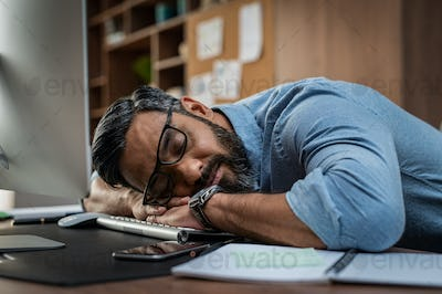 Tired businessman sleeping on computer desk