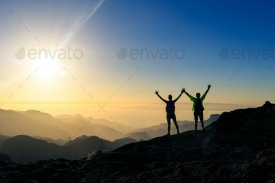 Couple hikers success and trust concept in mountains