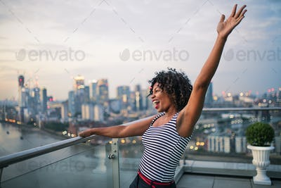 A portrait of businesswoman standing against London rooftop view panorama.