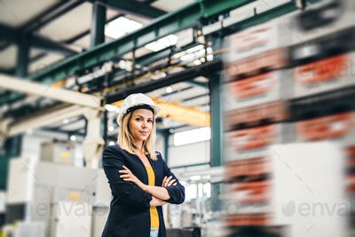 A portrait of an industrial woman engineer standing in a factory, arms crossed.