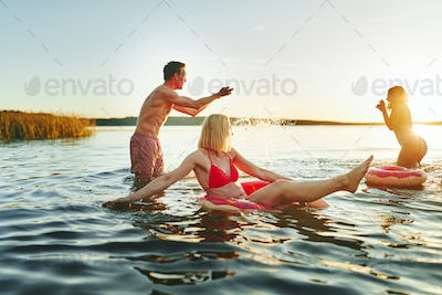 Laughing young friends splashing each other in a lake
