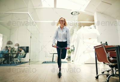Young businesswoman laughing while riding a scooter around her office