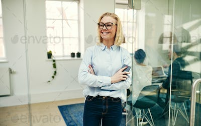 Smiling businesswoman leaning with her cellphone against an office wall
