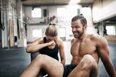 Fit people laughing while taking a break from working out