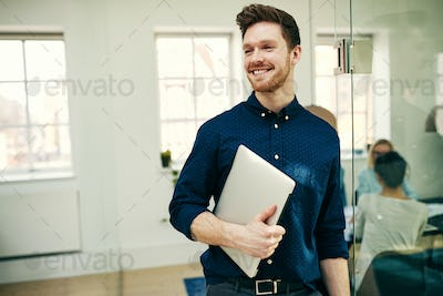 Smiling young businessman carrying a laptop in an office