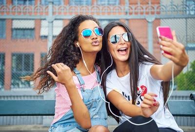 Smiling young girlfriends sitting outside taking selfies together