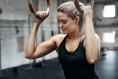Smiling young woman working out at the gym on rings