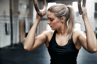 Fit young woman sweating during a gym workout with rings