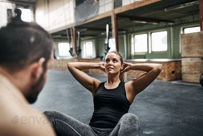 Young woman doing crunches with her male gym partner