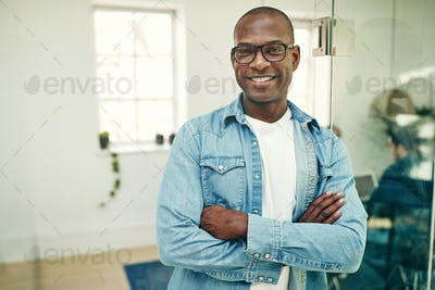 Smiling young African businessman working in a modern office