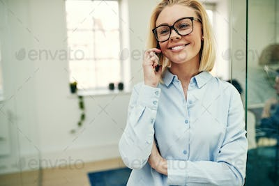 Smiling businesswoman standing in an office talking on a cellphone