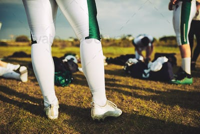 Closeup of football players on a field with their equipment