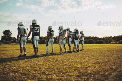 Football players standing in a line on an outdoor field