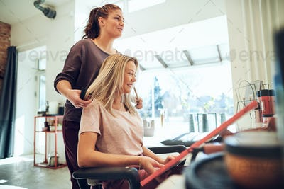 Smiling woman looking at hair color samples with her hairstylist