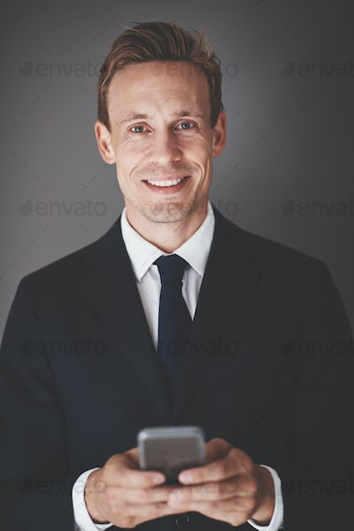 Smiling young business executive sending texts against a gray background