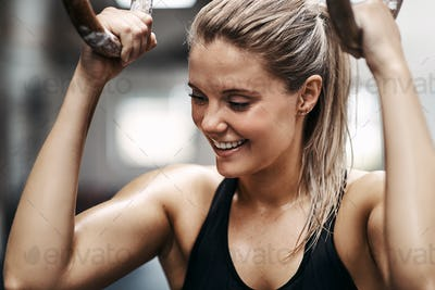 Young woman smiling during a ring workout at the gym
