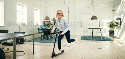 Laughing young businesswoman riding a scooter in a large office