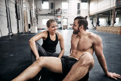 Two fit people relaxing on a gym floor after exercising
