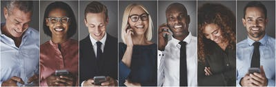 Diverse group of smiling business professionals using cellphones