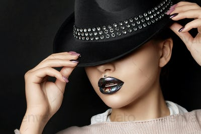 Young woman with fashion make up straightens her hat