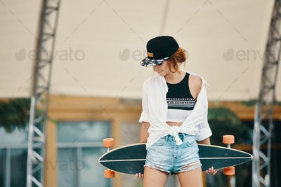 Stylish urban girl posing with Longboard